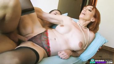 Lusty redhead amateur granny smiles as she rides a young raging dick
