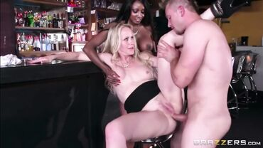 Ebony cougar helps a blonde MILF to have her ass fucked in a bar